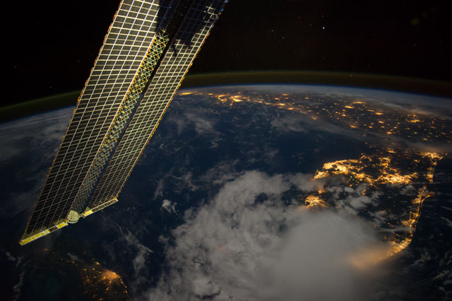 image at earth's horizon containing a solar panel, bright lights from cities, and a large weather pattern